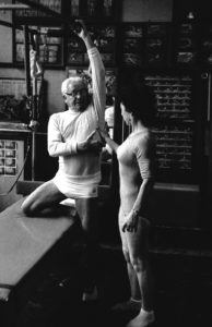 Joe Pilates shows client which muscle is engaging